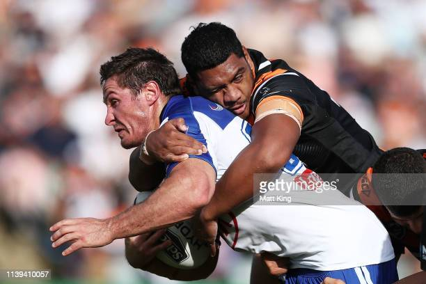 Josh Jackson of the Bulldogs is tackled during the round three NRL match between the Wests Tigers and the Canterbury Bulldogs at Campbelltown Stadium...