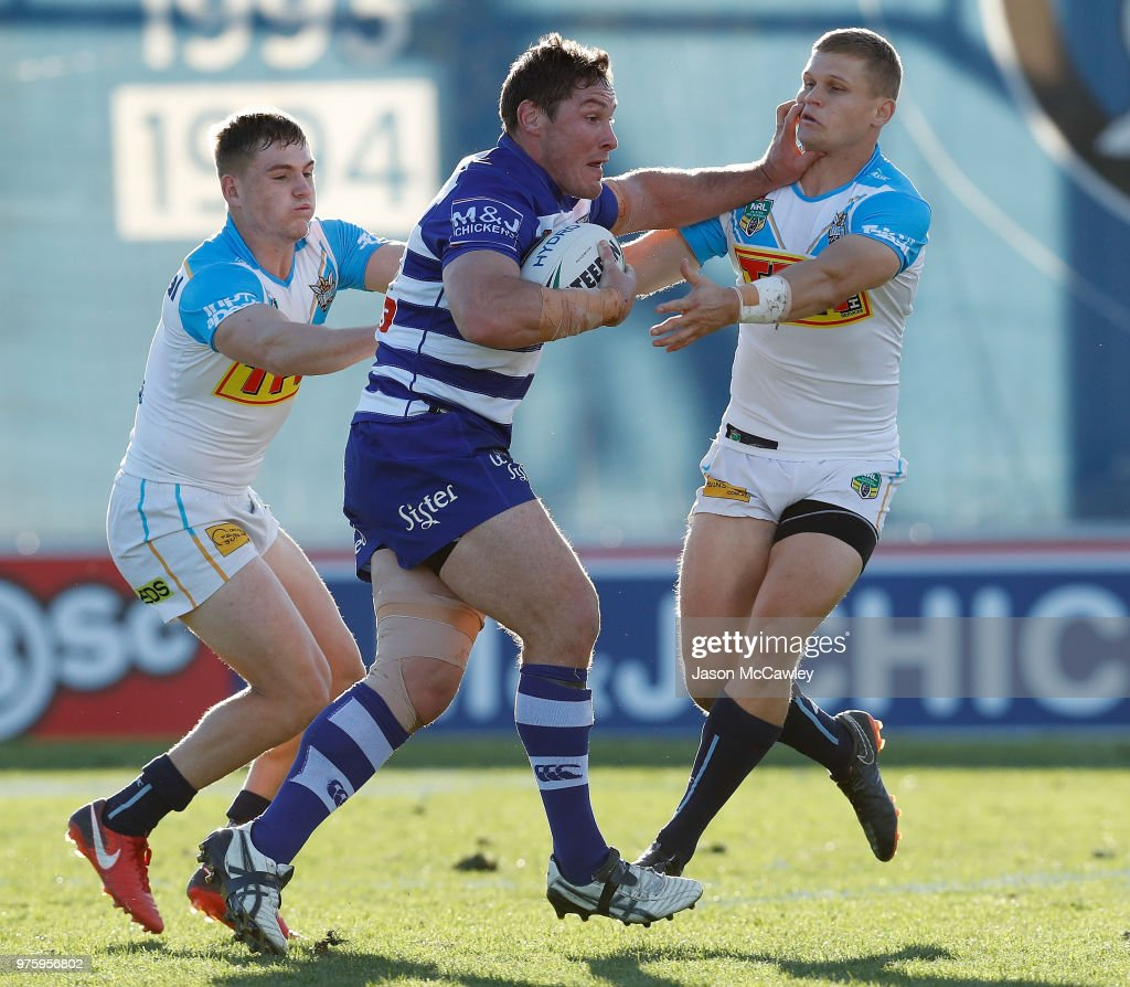 Josh Jackson of the Bulldogs puts a fend on Dale Copley of the Titans during the round 15 NRL match between the Canterbury Bulldogs and the Gold Coast Titans at Belmore Sports Ground on June 16, 2018 in Sydney, Australia.