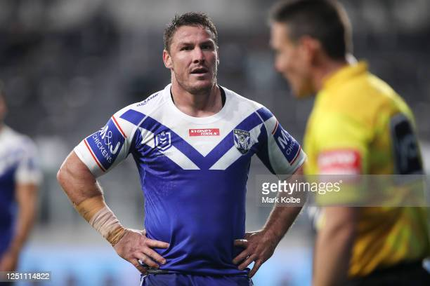 Josh Jackson of the Bulldogs waits to speak to referee Adam Gee looks on during the round six NRL match between the Cronulla Sharks and the...