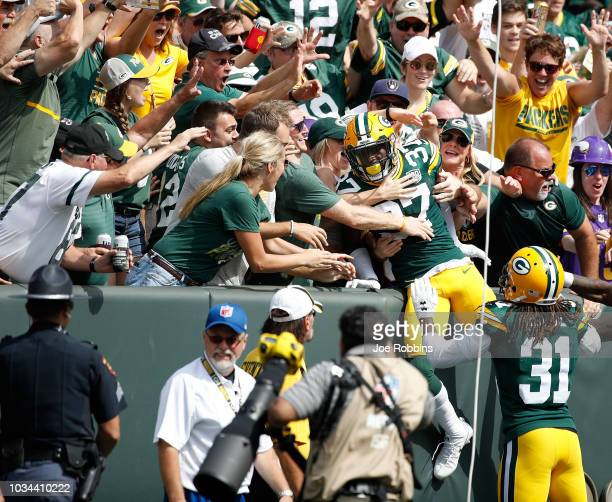 Josh Jackson of the Green Bay Packers celebrates with fans after scoring a touchdown on a blocked punt against the Minnesota Vikings during the first...