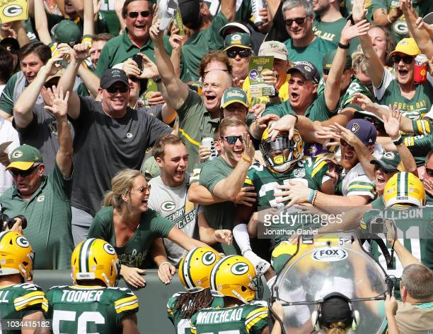 Josh Jackson of the Green Bay Packers celebrates with fans after scoring a touchdown on a blocked punt during the first quarter of a game against the...