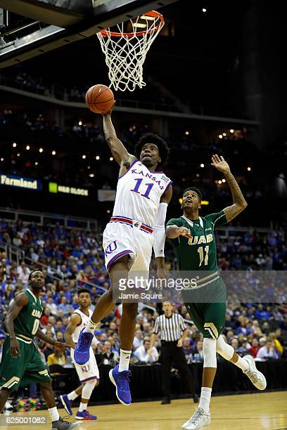 Josh Jackson of the Kansas Jayhawks goes up for a dunk as Dirk Williams of the UAB Blazers defends during the CBE Hall of Fame Classic game at the...