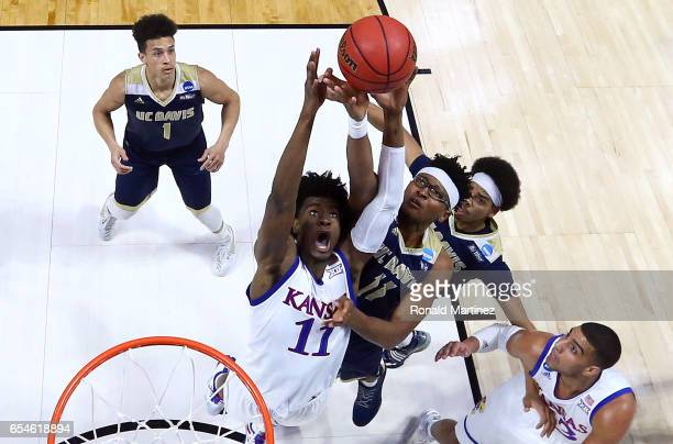 Josh Jackson of the Kansas Jayhawks jumps for a rebound with Chima Moneke of the UC Davis Aggies during the first round of the 2017 NCAA Men's...