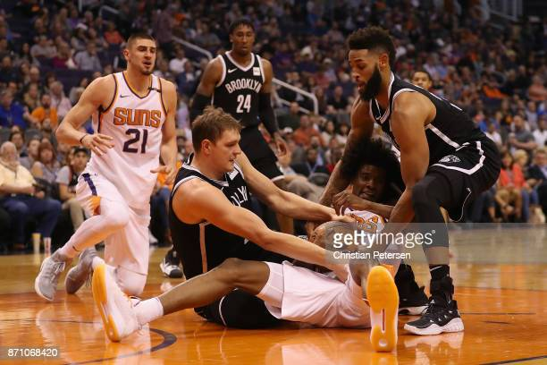 Josh Jackson of the Phoenix Suns battles for a loose ball with Timofey Mozgov and Allen Crabbe of the Brooklyn Nets during the first half of the NBA...