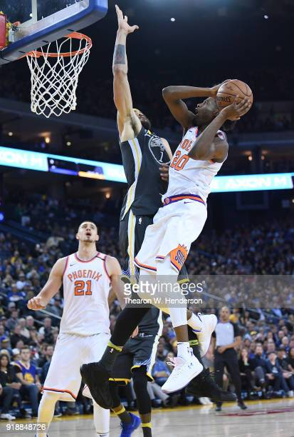 Josh Jackson of the Phoenix Suns drives to the basket and looks to get his shot off over the out stretched arm of JaVale McGee of the Golden State...