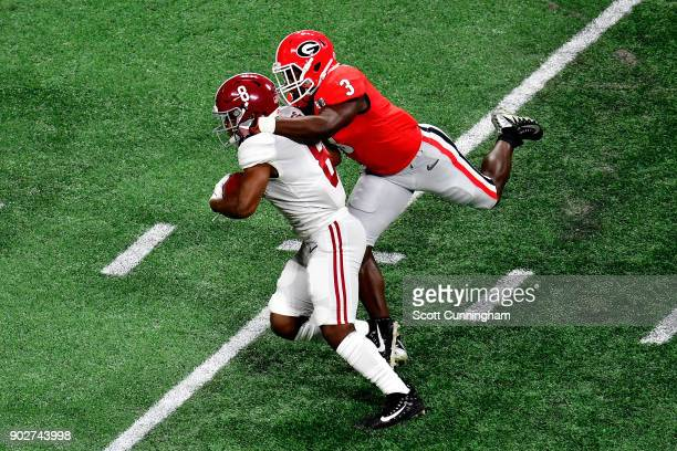 Josh Jacobs of the Alabama Crimson Tide is tackled by Roquan Smith of the Georgia Bulldogs after a catch during the first quarter in the CFP National...