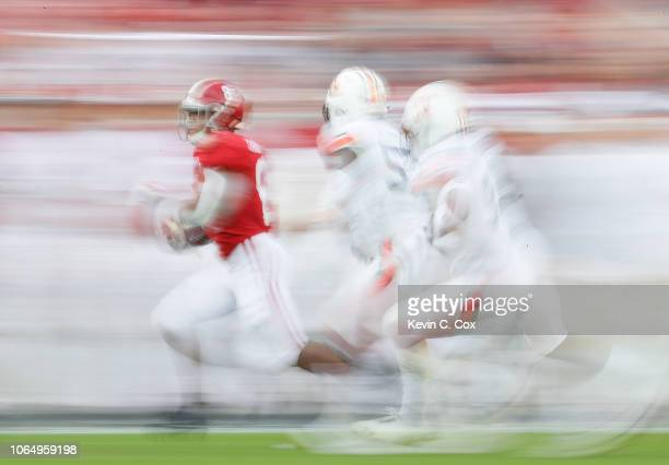 Josh Jacobs of the Alabama Crimson Tide rushes past Deshaun Davis and Noah Igbinoghene of the Auburn Tigers at BryantDenny Stadium on November 24...