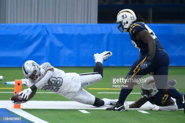 Josh Jacobs of the Las Vegas Raiders dives for a second quarter touchdown past Justin Jones and Nasir Adderley of the Los Angeles Chargers at SoFi...