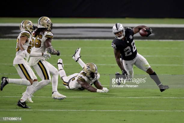 Josh Jacobs of the Las Vegas Raiders rushes down the field during the third quarter past Carl Granderson of the New Orleans Saints at Allegiant...