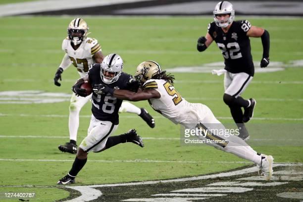 Josh Jacobs of the Las Vegas Raiders rushes past Demario Davis of the New Orleans Saints during the third quarter at Allegiant Stadium on September...