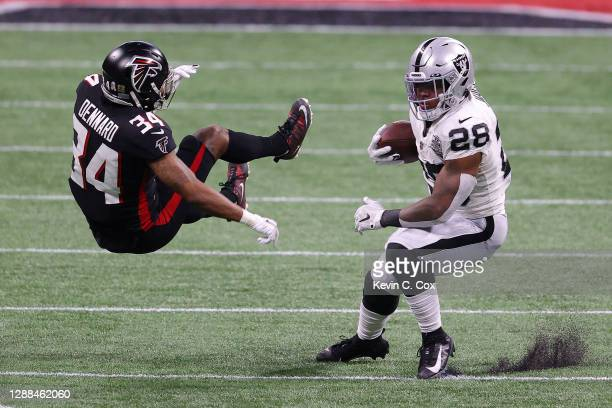 Josh Jacobs of the Las Vegas Raiders rushes with the ball against Darqueze Dennard of the Atlanta Falcons at MercedesBenz Stadium on November 29 2020...