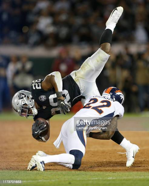 Josh Jacobs of the Oakland Raiders is tackled by Kareem Jackson of the Denver Broncos in the third quarter of the game at RingCentral Coliseum on...