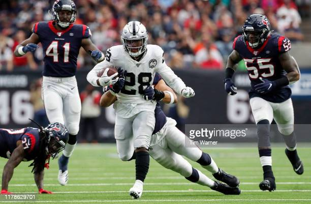 Josh Jacobs of the Oakland Raiders runs the ball defended by Brennan Scarlett of the Houston Texans in the second quarter at NRG Stadium on October...