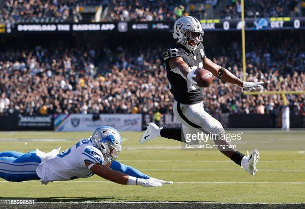 Josh Jacobs of the Oakland Raiders runs the ball in for a 2yard touchdown ahead of Miles Killebrew of the Detroit Lions in the first quarter at...