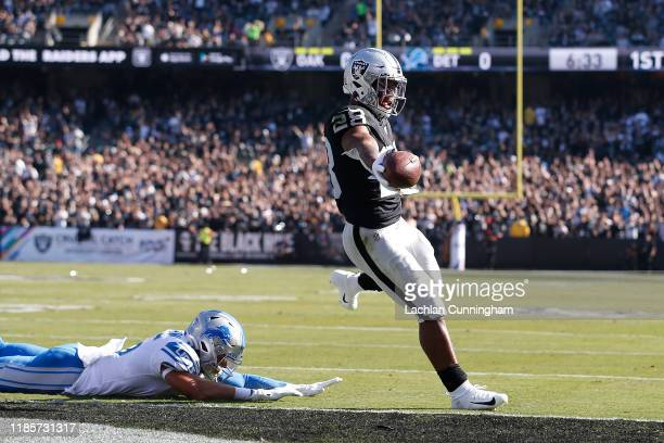Josh Jacobs of the Oakland Raiders runs the ball in for a 2-yard touchdown ahead of Miles Killebrew of the Detroit Lions in the first quarter at...