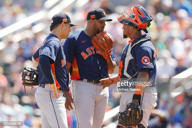 Josh James of the Houston Astros talks with Martin Maldonado and Aledmys Diaz against the Atlanta Braves during the first inning of a Grapefruit...