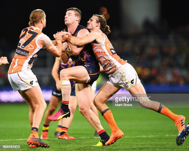 Josh Jenkins of the Adelaide Crows marks and trys to break through Harry Himmelberg and Phil Davis of the Giants and during the round 11 AFL match...