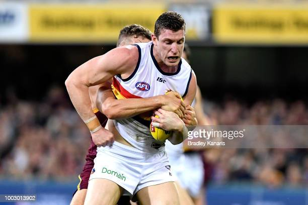 Josh Jenkins of the Crows is pressured by the defence of Tom Cutler of the Lions during the round 18 AFL match between the Brisbane Lions and the...