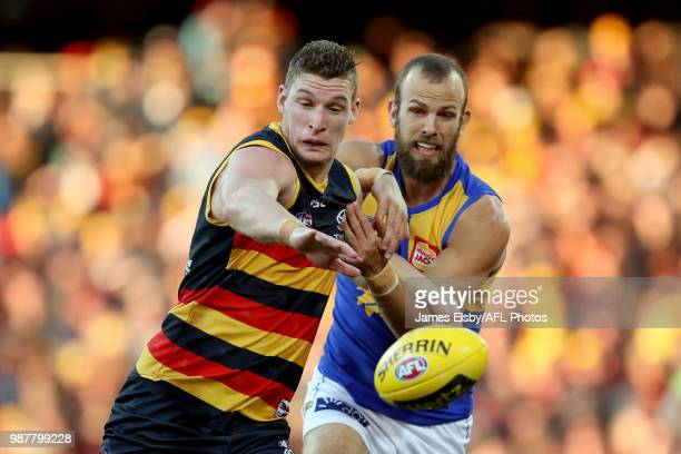 Josh Jenkins of the Crows is tackled by Will Schofield of the Eagles during the 2018 AFL round15 match between the Adelaide Crows and the West Coast...