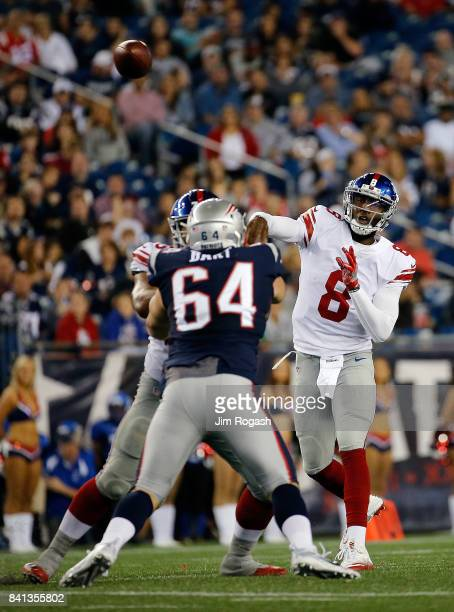 Josh Johnson of the New York Giants throws over Michael Bart of the New England Patriots in the first half during a preseason game at Gillette...