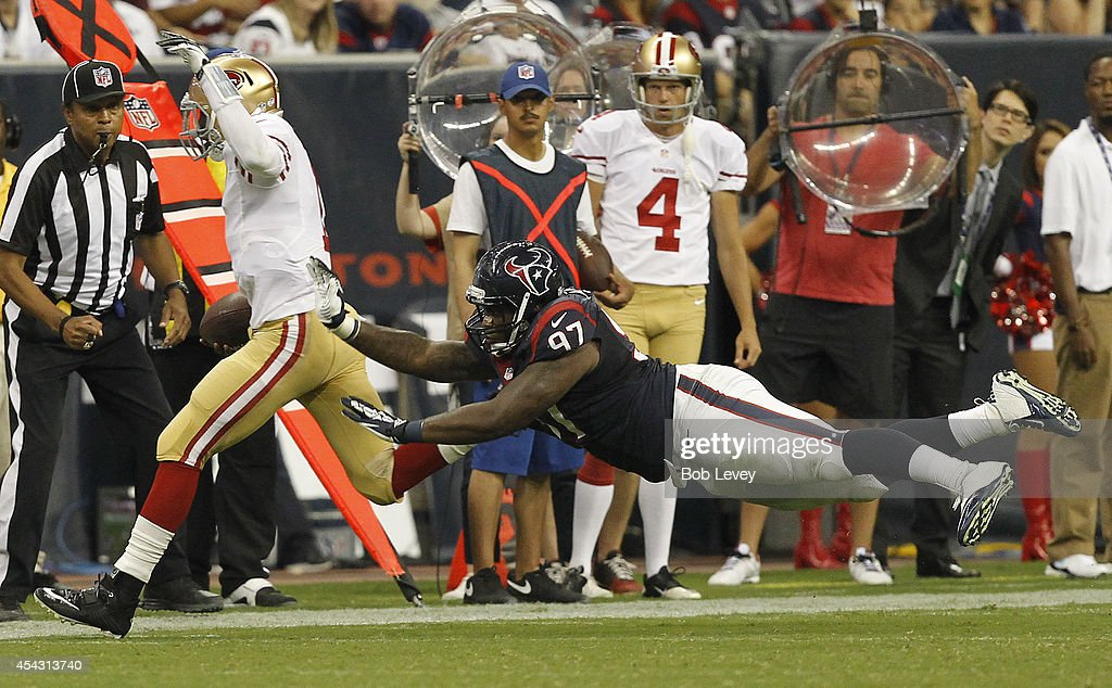 Josh Johnson #1 of the San Francisco 49ers is forced out of bounds by Jeoffrey Pagan #97 of the Houston Texans at Reliant Stadium on August 28, 2014 in Houston, Texas.
