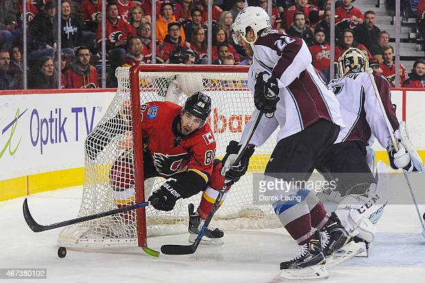 Josh Jooris of the Calgary Flames crashes the net of Semyon Varlamov of the Colorado Avalanche during an NHL game at Scotiabank Saddledome on March...