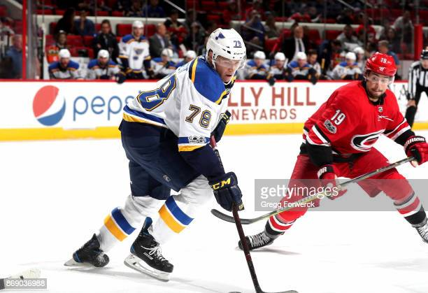 Josh Joorish of the Carolina Hurricanes defends against the Beau Bennett of the St Louis Blues during an NHL game on October 27 2017 at PNC Arena in...