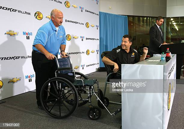 Josh Katz pushes the wheelchair of Tony Stewart NASCAR Sprint Cup Series driver and coowner of StewartHaas Racing before he speaks to the media in...