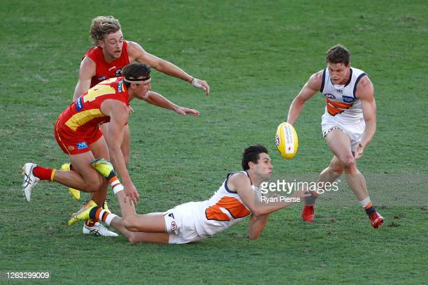 Josh Kelly of the Giants handballs whilst being tackled during the round nine AFL match between Gold Coast Suns and the Greater Western Sydney Giants...