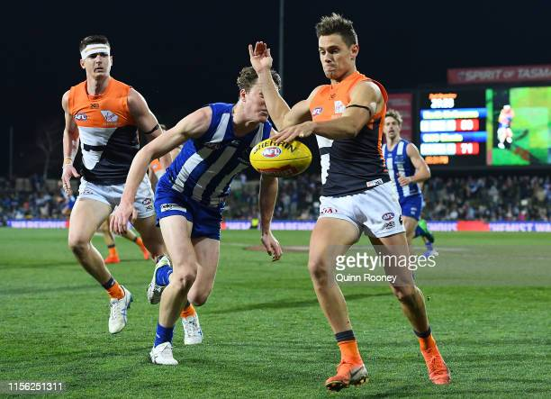 Josh Kelly of the Giants kicks whilst being tackled by Nick Larkey of the Kangaroos during the round 13 AFL match between the North Melbourne...