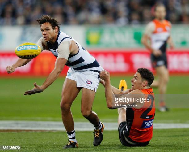 Josh Kelly of the Giants tackles Steven Motlop of the Cats during the round 23 AFL match between the Geelong Cats and the Greater Western Sydney...