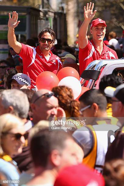 Josh Kennedy and Ted Richards of the Swans wave to the crowd during the 2014 AFL Grand Final Parade on September 26 2014 in Melbourne Australia