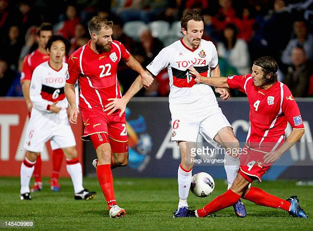 Josh Kennedy of Nagoya is challenged by Jonathan Mckain and Iain Fyfe of Adelaide United during the AFC Asian Champions League match between Adelaide...
