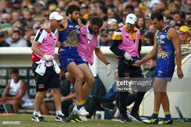 Josh Kennedy of the Eagles is assisted from the field with a lower leg injury during the round 10 AFL match between the West Coast Eagles and the...