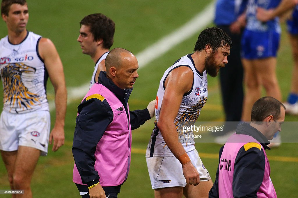 Josh Kennedy of the Eagles is assisted to the bench after receiving a heavy knock in a marking contest during the round 11 AFL match between the West Coast Eagles and the North Melbourne Kangaroos at Patersons Stadium on June 1, 2014 in Perth, Australia.