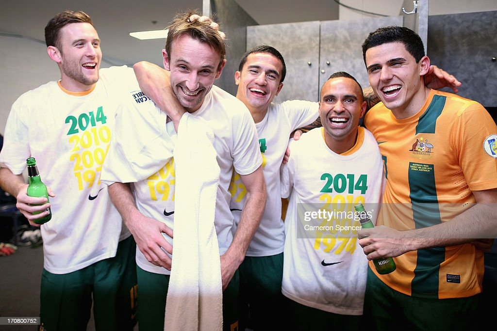 Josh Kennedy of the Socceroos is embraced by Tim Cahill and team mates in the Socceroos changeroom after winning the FIFA 2014 World Cup Asian Qualifier match between the Australian Socceroos and Iraq at ANZ Stadium on June 18, 2013 in Sydney, Australia.