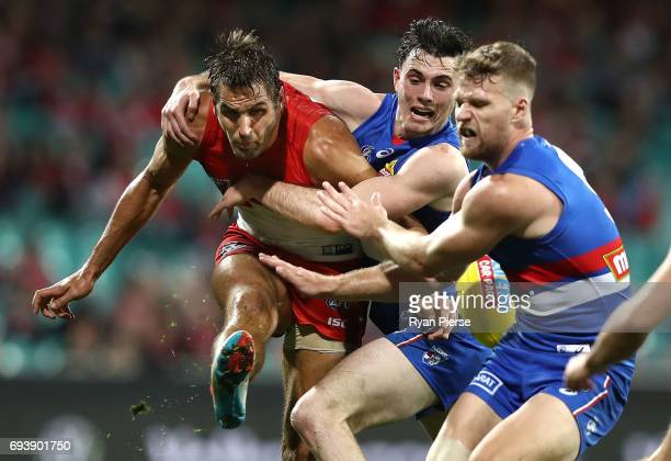 Josh Kennedy of the Swans kicks under pressure during the round 12 AFL match between the Sydney Swans and the Western Bulldogs at Sydney Cricket...