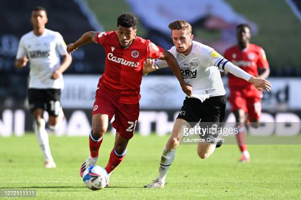 Josh Laurent of Reading FC and Max Bird of Derby County battle for the ball during the Sky Bet Championship match between Derby County and Reading at...