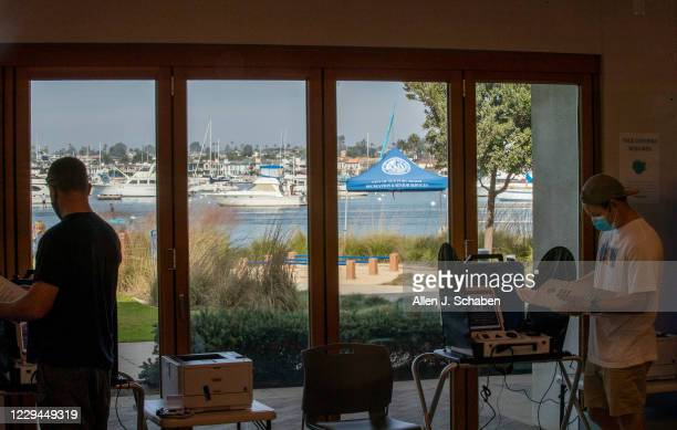 Josh Leith, right, of Newport Beach, has a scenic view of Newport Harbor while voting at Marina Park Community Center on election day Tuesday, Nov....