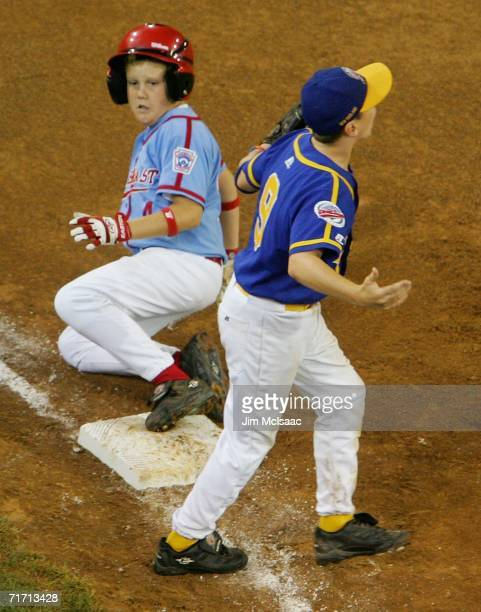 Josh Lester of the Southeast team from Georgia slides safely into third for a three run triple in the second inning as Matthew Feeney of the New...