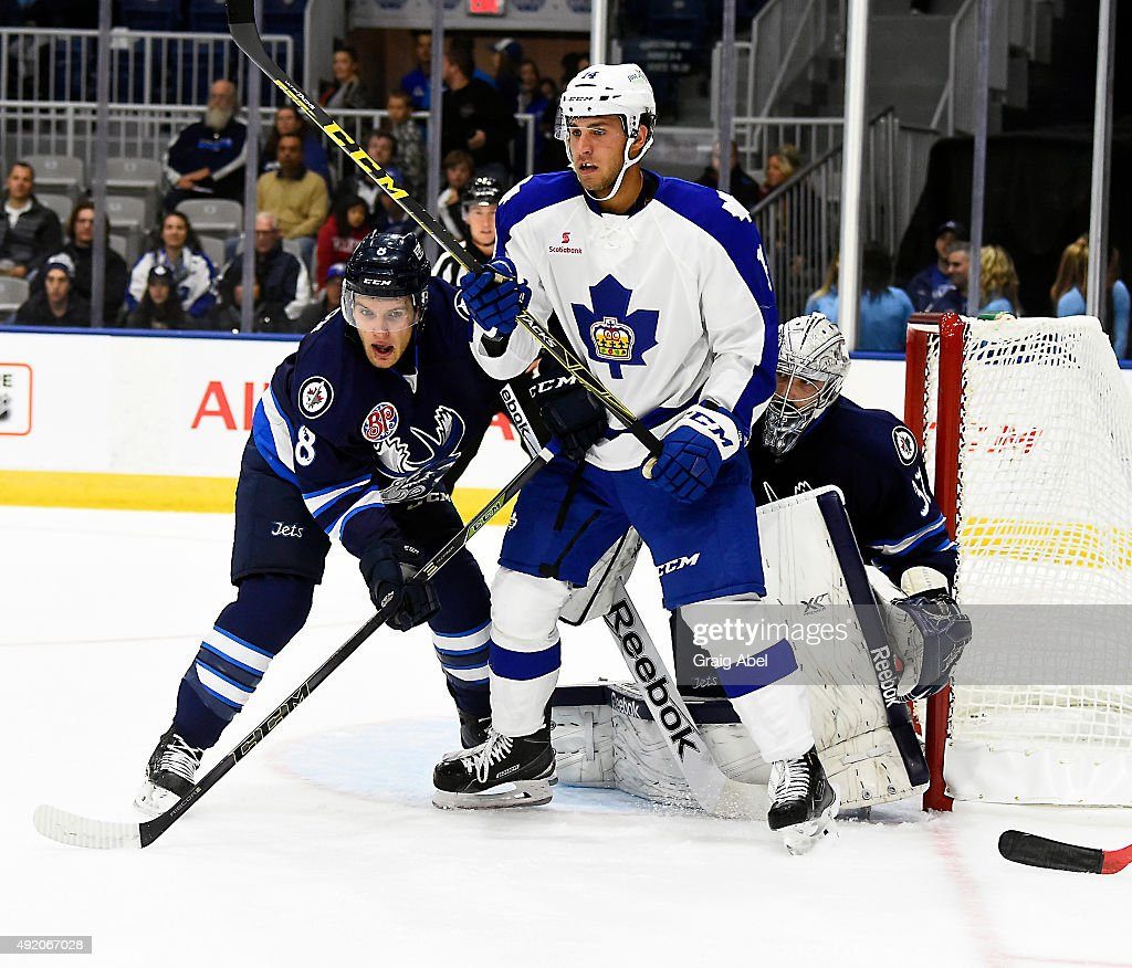 Josh Levio #14 of the Toronto Marlies fights for space with Brenden Kichton #8 and goalie Connor Hellebuyck #37 of the Manitoba Moose during Opening Night AHL game action on October 9, 2015 at the Ricoh Coliseum in Toronto, Ontario, Canada.