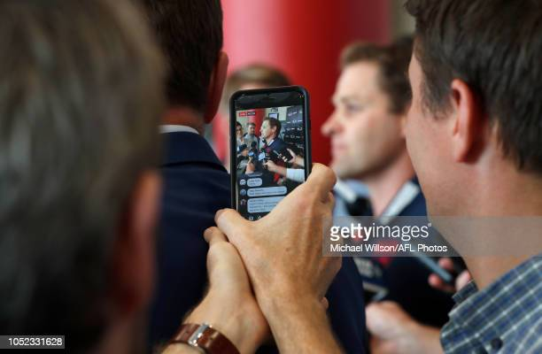 Josh Mahoney GM of Football Operations of the Demons is seen through a smartphone during the AFL Trade period final day at Marvel Stadium on October...