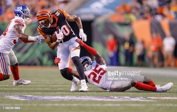 Josh Malone of the Cincinnati Bengals runs the ball after a catch as Corey Ballentine of the New York Giants tries to make the stop during the...
