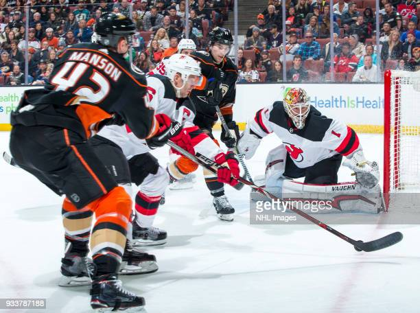 Josh Manson of the Anaheim Ducks and Andy Greene of the New Jersey Devils battle for the puck as Adam Henrique of the Ducks goalie Keith Kinkaid of...