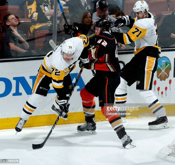 Josh Manson of the Anaheim Ducks battles for position against Patric Hornqvist and Evgeni Malkin of the Pittsburgh Penguins during the game on...