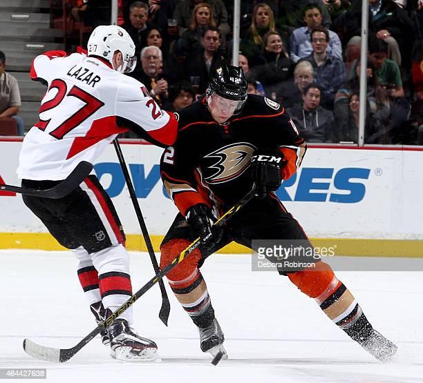 Josh Manson of the Anaheim Ducks battles for the puck against Curtis Lazar of the Ottawa Senators on February 25 2015 at Honda Center in Anaheim...