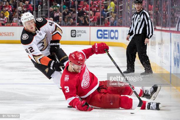 Josh Manson of the Anaheim Ducks battles with Nick Jensen of the Detroit Red Wings during an NHL game at Little Caesars Arena on February 13 2018 in...