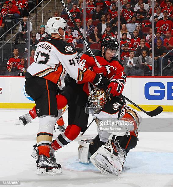 Josh Manson of the Anaheim Ducks checks Adam Henrique of the New Jersey Devils into John Gibson during the second period at the Prudential Center on...