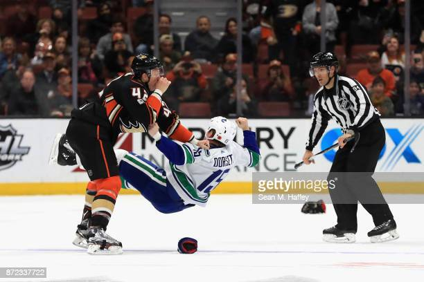 Josh Manson of the Anaheim Ducks fights Derek Dorsett of the Vancouver Canucks as linesman Bryan Pancich looks on during the third period of a game...