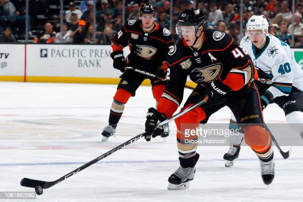 Josh Manson of the Anaheim Ducks skates with the puck with pressure from Antti Suomela of the San Jose Sharks during the game on October 28 2018 at...
